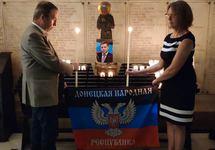 Юбер Файяр зажигает свечу в память Александра Захарченко. Фото из твиттера политика